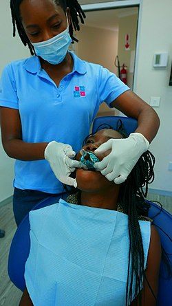 Zambian orthodontist working on a Cameroonian in Lusaka.jpg