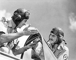 Two men in flying goggles talking beside an aircraft cockpit.