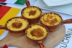 Four small clay pots covered with grated cheese, served on a table after baking