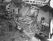 Soldiers with guns and civilians in white walk through the rubble of a white building demolished in an explosion. Pieces of wood, bent metal lie strewn on the ground. The roof has fallen off except for the support beams.