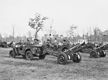 Small motor vehicles towing artillery guns across a grassed area. Trees are visible in the background.