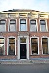 Eclectisch, in schoonwerk opgetrokken, blokvormig pand met verdieping onder met pannen gedekt omlopend schilddak