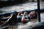 A security policeman maneuvers under barbed wire on a very muddy portion of the obstacle course during Exercise Volant Rodeo '84 DF-ST-85-05750.jpg
