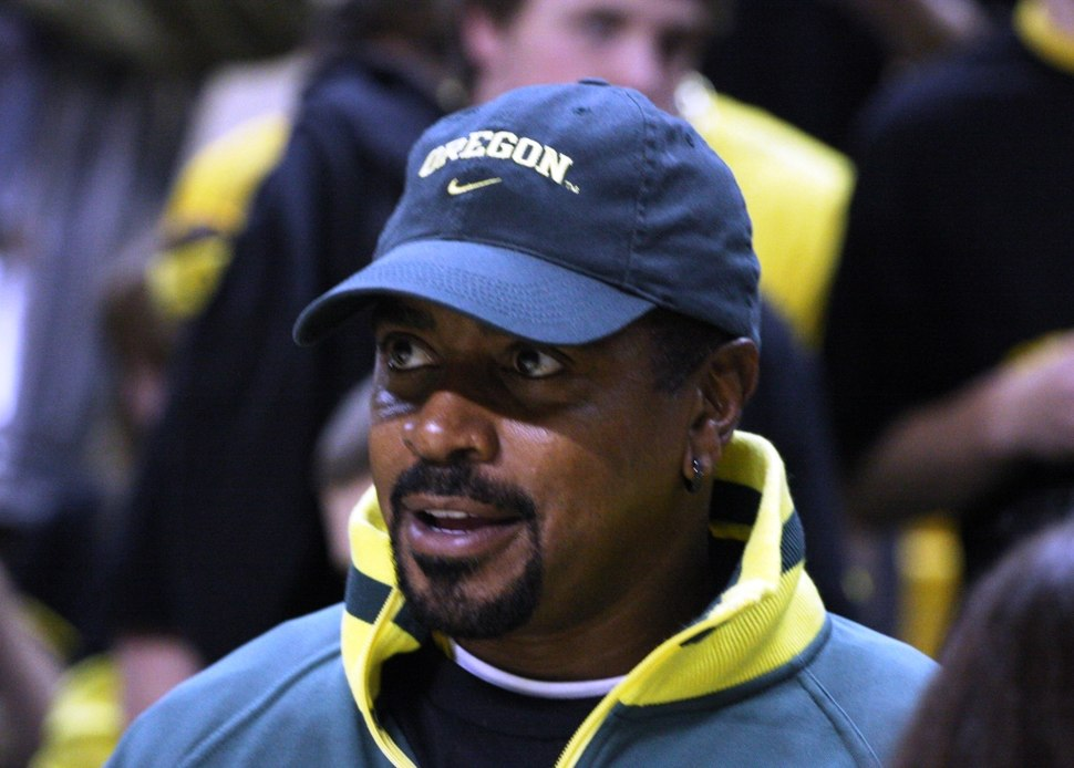 Candid head and shoulders photograph of Rashad wearing a baseball cap bearing the Oregon Ducks logo