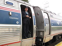An Amtrak conductor standing in the doorway of an Amfleet cars with its trapdoor in the closed position