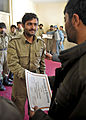An Afghan Local Police (ALP) graduate receives an ALP patch and certificate during a graduation ceremony at the Shah Joy district center in Zabul province, Afghanistan, Jan 120129-N-CI175-102.jpg