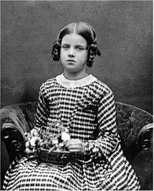 Dreiviertel-Studiofoto eines sitzenden Mädchens, ungefähr neun Jahre alt, leicht prall und ziemlich feierlich aussehend, in einem gestreiften Kleid, einen Blumenkorb auf dem Schoß haltend.
