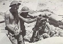 Soldiers loading a mortar tube in a desert position