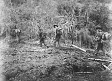 Soldiers patrol through a jungle setting, passing a makeshift grave marker made out of bamboo