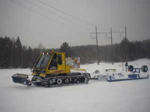Bombardier Recreational Products - Bombardier BR180 snowcat pulling snowmobile trail groomer attachment