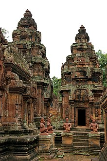 Ancient Cambodian open-air temple, featuring four statues of seated figures in the middle distance.