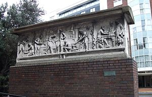 Barbican Estate - Frieze recovered from Bryers and Sons building at 53 and 54 Barbican. The building survived wartime bombing but was demolished to make way for the redevelopment. The Frieze was preserved as a monument