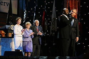 BeBe Winans - President George W. Bush with his arm around Winans as he sings God Bless America during the 'Saluting Those Who Serve' event, January 18, 2005. Also pictured are, from left, Laura Bush, Lynne Cheney, and Vice President Dick Cheney.