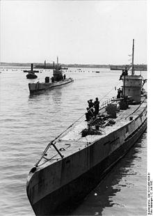 Черно-белая фотография двух подводных лодок времен Второй мировой войны на поверхности моря.  На заднем плане видна земля.