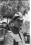 A man in semi profile standing in front of a tree and wearing a military uniform, peaked cap and a neck order in the shape of a cross. His cap has an emblem in shape of a human skull and crossed bones.