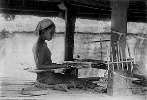 Loom - A teenager working a backstrap loom in 1920s Bali