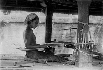 Loom - A teenager working a backstrap loom in 1920s Bali