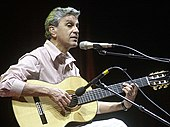A white man with gray hair, wearing a striped shirt with white and pink colors, holding an acoustic guitar with two microphones in front of him.