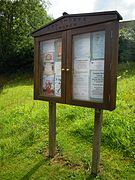 The village notice board which stands outside the boundary wall of the parish church of Our Lady and Saint Margaret.