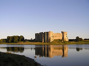 Carew Castle - Domestic Tudor-period ranges from across the mill pond to the north west