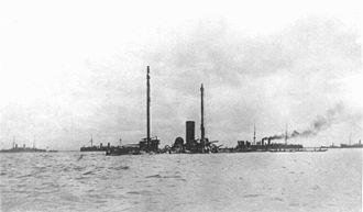 Spanish cruiser Castilla - The wreck of Castilla, with Dewey's squadron and merchant ships in the background.
