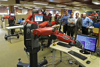 Rodney Brooks - Robot at Rethink Robotics, 2013. Brooks is at the right in the lineup behind the robot. At left is Steve Jurvetson, the photographer.