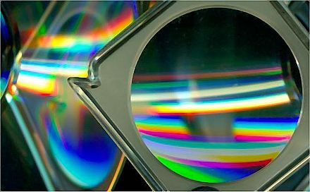 A magnifying glass and CD-ROM discs placed at an angle to the bed show reflection, refraction, and diffraction effects that can be generated. Cds and lens.jpg