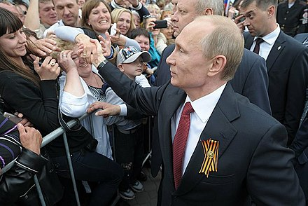 Putin, with St. George ribbon, greets local residents during a visit to the Crimean city of Sevastopol on 9 May 2014 Celebrating Victory Day and the 70th anniversary of Sevastopol's liberation (2493-19).jpg