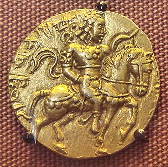 Chandragupta II - An 8 gm gold coin featuring Chandragupta II astride a caparisoned horse with a bow in his left hand.