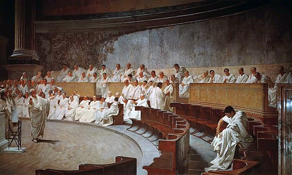 Representation of a sitting of the Roman senate: Cicero attacks Catiline, from a 19th-century fresco in Palazzo Madama, Rome, house of the Italian Senate. It is worth noting that idealistic medieval and subsequent artistic depictions of the Senate in session are almost uniformly inaccurate. Illustrations commonly show the senators arranged in a semicircle around an open space where orators were deemed to stand; in reality the structure of the existing Curia Julia building, which dates in its current form from the Emperor Diocletian, shows that the senators sat in straight and parallel lines on either side of the interior of the building. In current media depictions in film this is shown correctly in The Fall of the Roman Empire, and incorrectly in, for example, Spartacus. Ciceron denuncia a Catilina, por Cesare Maccari.jpg