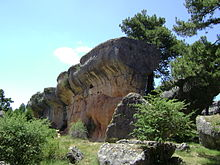 One of Ciudad Encantada's rock formations: The top of this wall of stone is rounded and wider than its base; sparse forestation surrounds the formation.