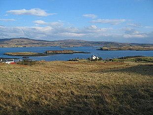A long view of the house by the jetty with several of the islands in Loch Dunvegan behind