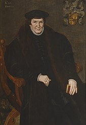 Portrait of a large man, seated, holding a book