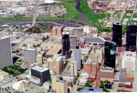Elevated image showing various buildings in the foreground and middleground with various degrees of broken windows