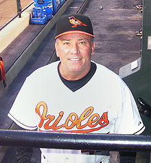 "A man wearing a white baseball jersey with ""Orioles"" written across the chest in orange script and a black baseball cap with an orange oriole on the front"