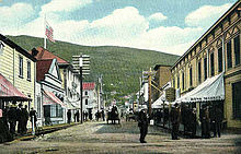 Dawson city in 1899. Modern houses, horse carriage and telegraph lines seen in street.