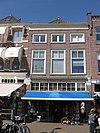 foto van Pand onder schilddak en met aan de markt een voorgevel met lage bovenverdieping onder rechte lijst