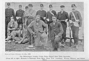 Dog Tax War - The Mahurehure leaders under police guard after their surrender (From left to right—Romana te Paehangi, Hone Mete, Hone Toia (standing), Wiremu Makara, and Rekini Pehi.)