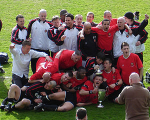 F.C. United players and coaches celebrate winning their first championship title. The championship trophy is seen on the green grass pitch and the group have their arms around one another.