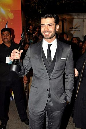 A smiling Khan, holding a statuette