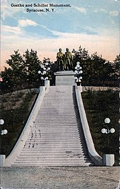 "Photograph of an old color postcard. There is printing at the top left of the postcard that says ""Goethe and Schiller Monument, Syracuse, N.Y."" The picture shows a statue of two men on a stone pedestal. The statue is at the top of a slope, and is approached by a long, wide stairway. There are several lighting fixtures on each side of the stairway, and there are formal plantings of shrubbery on both sides. There are trees behind the statue."
