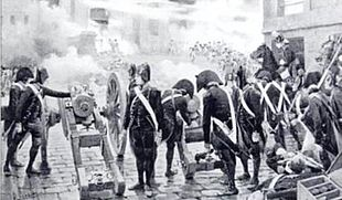 Black and white print shows artillerists loading and firing cannons in the street. The gunners wear dark uniforms with white belts and black bicorne hats.