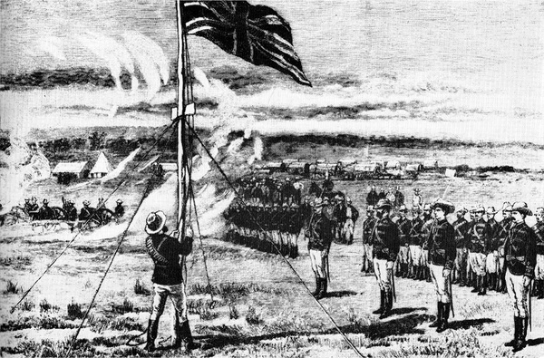 The Union Jack is raised atop a hill by a man in military uniform. Officers and men in the same uniform stand to attention. Covered wagons and makeshift buildings can be seen in the background.
