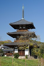 Wooden three-storied pagoda with white walls and railed verandas on the upper floors.