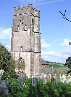 Square stone tower with gravestones in the foreground.