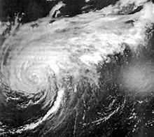 Black and white image of a hurricane. Rainbands to the top of the hurricane are extended out to the upper-right, and the center of the hurricane itself is located at center-left. Clouds appear as shades of white and the sea as shades of black. However, sunglint is visible at center-right.