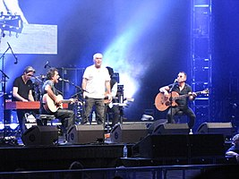 A stage shot with four men clearly visible. The man at left is leaning at a rectangular box, he has a microphone nearby. The second man is shown in right profile, he is playing a guitar and singing into a microphone while seated. The third man is standing in the middle of the stage with a arms at his sides, he carries a microphone in his right hand. The fourth man is also seated while playing a guitar and at a microphone. A fifth man is obscured seated behind and to the right of the middle one. The men are surrounded by stage equipment including speakers, lights and additional microphones. A drum kit is partly visible but the drummer is obscured.