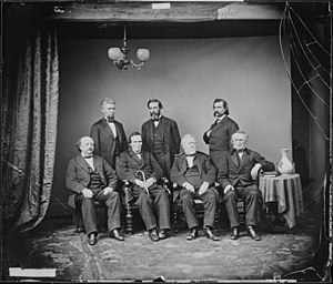 Impeachment of Andrew Johnson - Johnson Impeachment Committee from a photograph by Mathew Brady in the Signal Corps, War Department, Washington. Left to right, Seated: Benjamin F. Butler, Thaddeus Stevens, Thomas Williams, John A. Bingham. Standing: James F. Wilson, George S. Boutwell, John A. Logan.