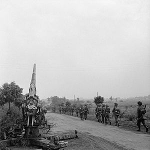 Army Reserve (United Kingdom) - Infantry of 50th (Northumbrian) Division moving up past a knocked-out German 88mm gun near 'Joe's Bridge' over the Meuse-Escaut Canal in Belgium, 16 September 1944