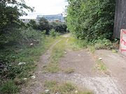 An overgrown ramp slopes down to a grass area with a railway track & signal. The ramp has 2 gravel tracks where a vehicle has been. In the distance is a modern office tower.